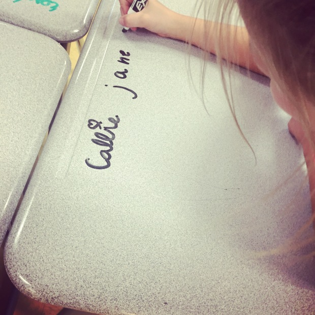Callie writes her name on desk